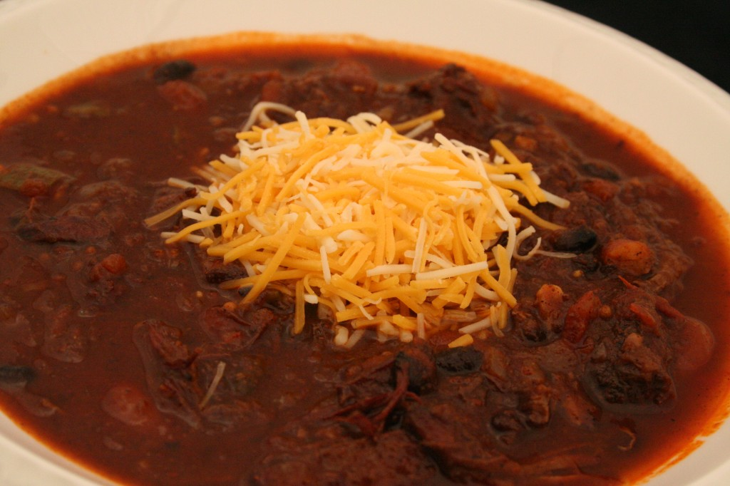 Chili in a bowl stacked with cheese